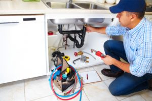 Plumber in Hamilton fixing a kitchen sink clogged drain
