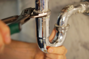Close up of a Hamilton plumber fixing a clogged drain