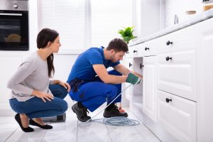 Woman watching a professional plumber use rooter service to clear clogged drain