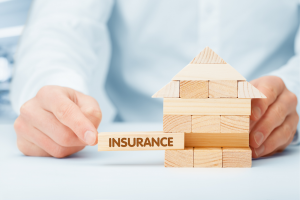 Close up of a small house made of wooden blocks with 'insurance' written on one
