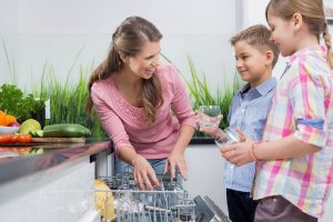 A mom showing her kids how to fill a dishwasher