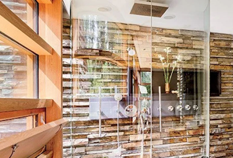 A walk-in curved, glass shower enclosure with jalousie windows