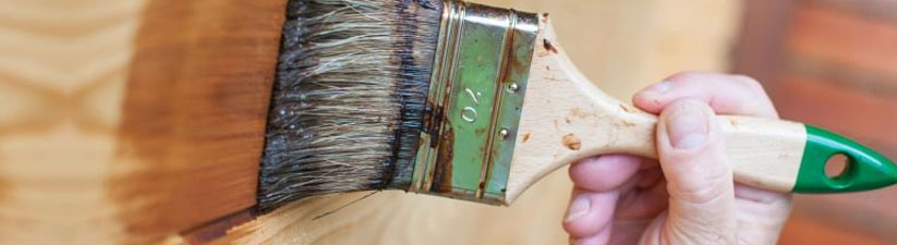 Close up of a person using a brush to apply varnish on wood