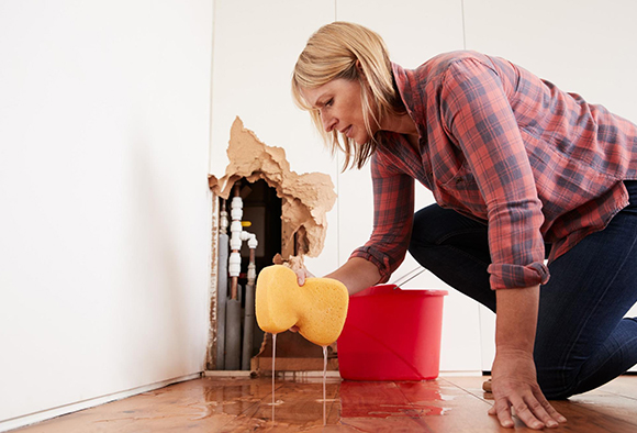 A homeowner cleaning up the puddle from a pipe leakage