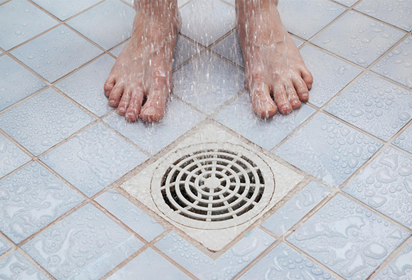 Close up of feet standing next to a shower drain