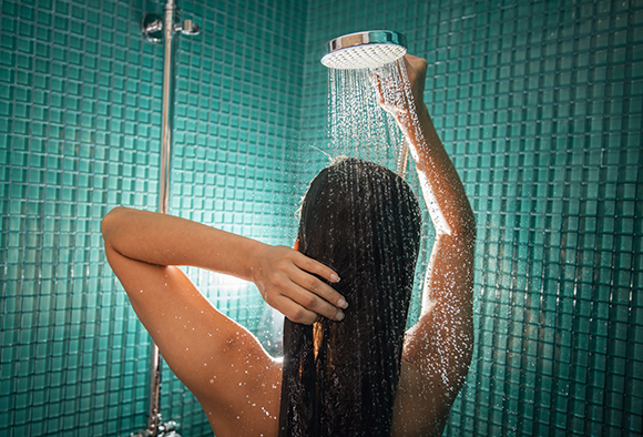 A woman washes her hair in the shower with soft water