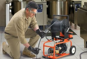 A plumber using a hydro-jetting machine on a floor drain