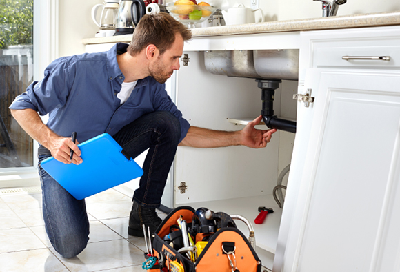 A plumber looking at the kitchen sink's pipes
