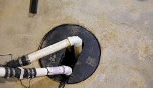A covered sump pump on the basement floor