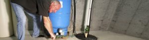 A man applying finishing touches on a newly-installed sump pump