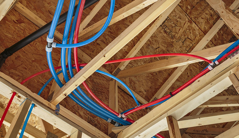 Red and blue pipes installed into a home under construction