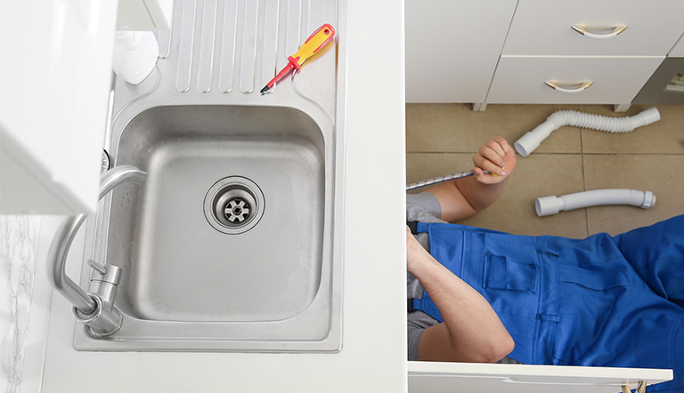 A plumber installs a kitchen faucet and sink
