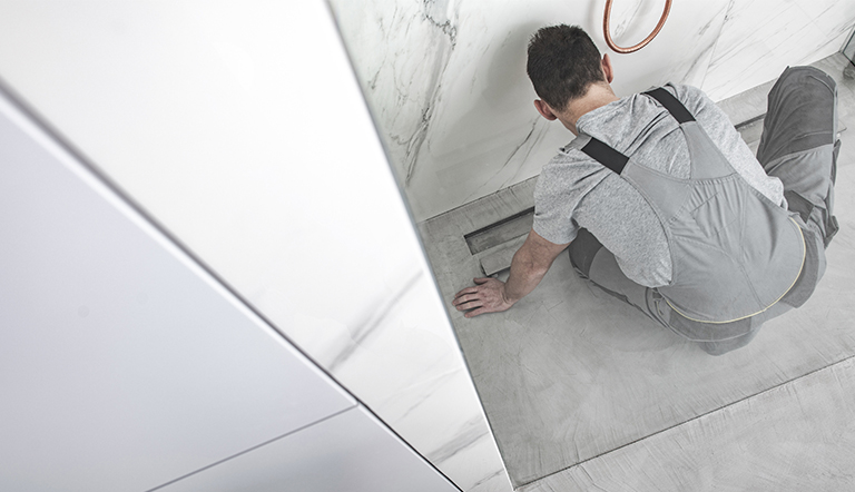 A plumber checks a shower drains smell