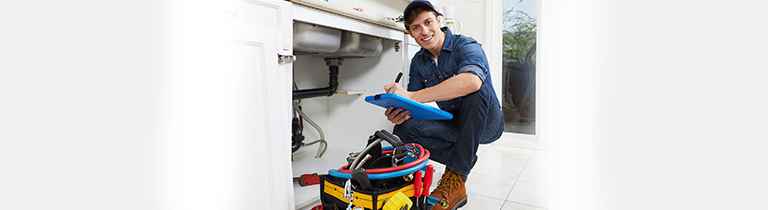 Friendly plumber hunkered beside a kitchen drain with drain cleaning equipment