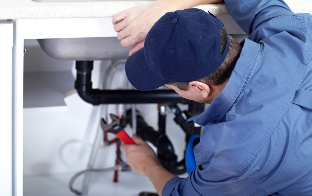 Closeup of a plumber working on a sink drain