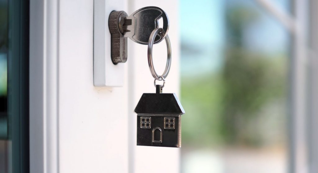 The keys to a new home on a doorknob with a house keychain